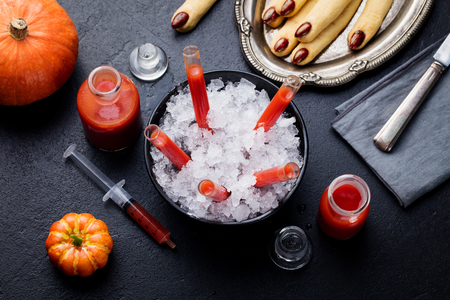 Bloody Mary cocktail in glass tubes with Witch fingers cookies for Halloween party celebration.