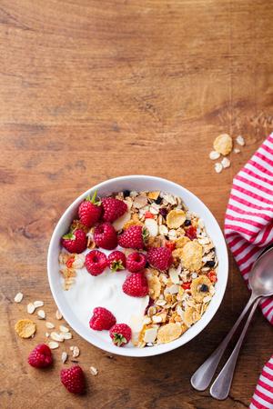 Healthy breakfast. Fresh granola, muesli with yogurt and berries on wooden