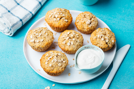 Oat muffins, apple and banana cakes with sour cream on a white plate.