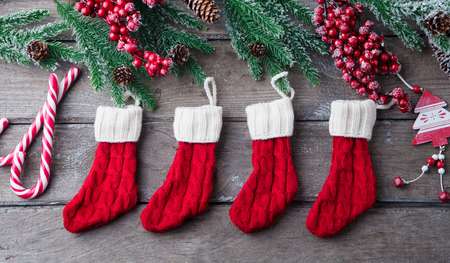 Fir tree decorated with socks, candy canes. Grey wooden Stockfoto