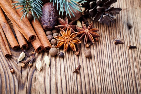 Christmas winter spices and blue pine tree branch on wooden