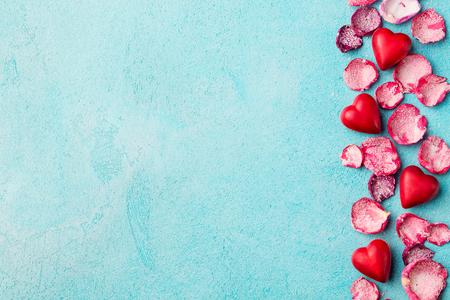 Schokoladenbonbons in Herzform mit kandierten, gezuckerten Rosenblüten.