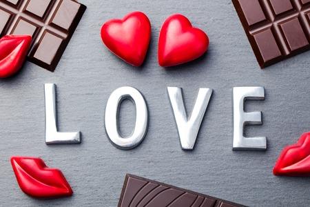 Love word, heart and lips shaped chocolate candies with chocolate bars on slate