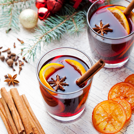 Mulled red wine with spices, orange slices on grey stone new year and Christmas