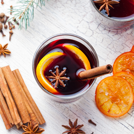 Mulled red wine with spices, orange slices on wooden new year and Christmas