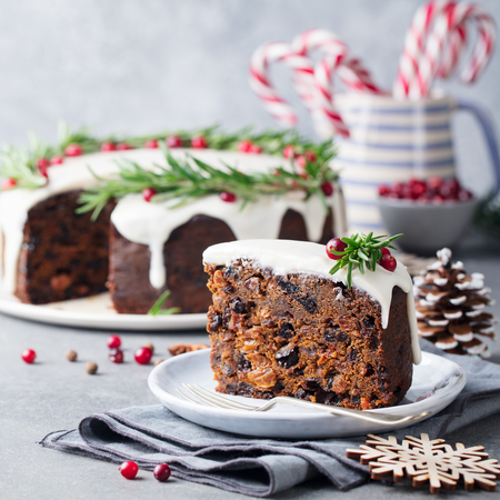 Christmas fruit cake, pudding on white plate. Traditional New Year dessert.