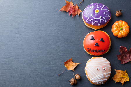 Donuts with Halloween decoration, icing on black slate