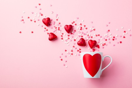 Mug with sugar and chocolate hearts on pink
