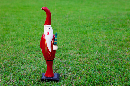 Christmas Santa Claus, wooden figure. Christmas and New Year celebration on tropical vacation. Copy space.