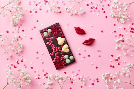 Chocolate bar, heart and lips candies with white flower.