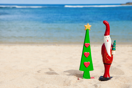 Christmas tree and Santa Claus, wooden figures, on a tropical beach