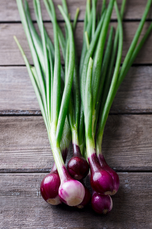 Red onion with fresh green sprouts on wooden Stockfoto