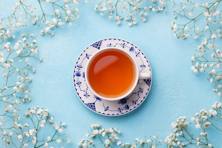 Cup of tea with fresh flowers on blue Stockfoto