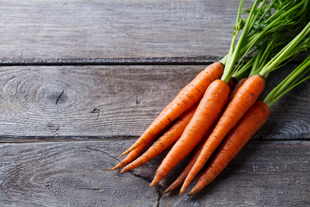 Fresh carrots bunch on a grey wooden