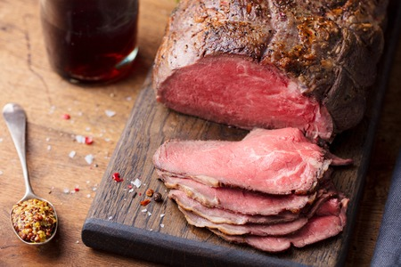 Roast beef on cutting board with glass of wine.