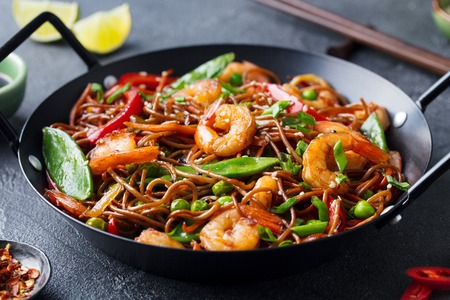 Stir fry noodles with vegetables and shrimps in black iron pan.