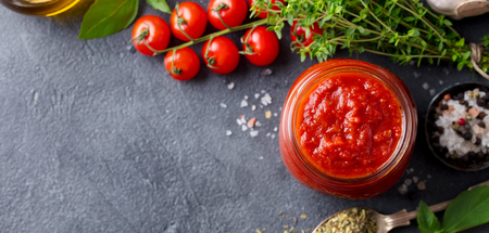 Traditional tomato sauce in a glass jar with fresh herbs, tomatoes and olive oil. Top view.