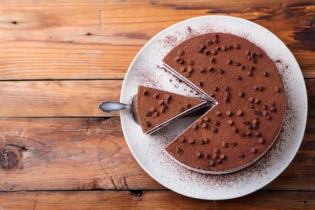 Tiramisu cake with chocolate decoration on a plate.