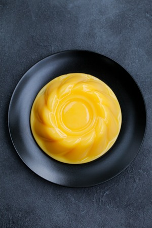 Mango pudding, jelly, dessert on black plate.