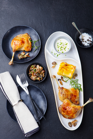 Duck legs confit with potato gratin and mushroom sauce. Top view Stockfoto