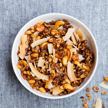 Healthy breakfast. Fresh granola, muesli with coconut, banana and nuts in a white bowl on grey textile
