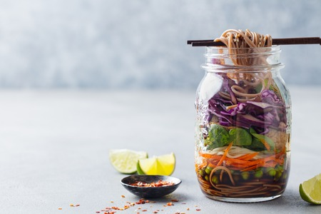 Healthy asian salad with noodles, vegetables, chicken and tofu in glass jars.
