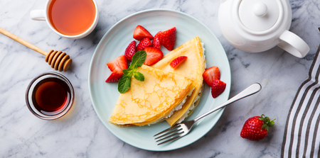 Crepes, thin pancakes with cream cheese, ricotta and fresh strawberries. Stock Photo