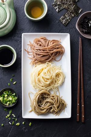 Assortment of Japanese soba noodles with sauce and garnishes.