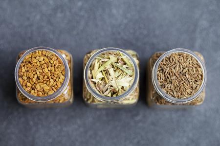 Spices in jars, lemongrass, fenugreek, cumin seeds.