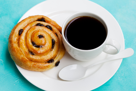 Fresh danish pastry with raisins with a cup of black coffee on blue table