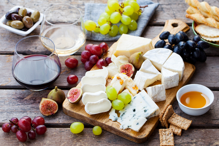 Cheese and fruits assortment on cutting board with red, white wine on wooden