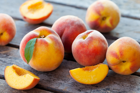 Fresh peaches, fruits on grey wooden