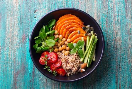 Healthy vegetarian salad. Roasted pumpkin, quinoa, tomatoes, green salad.