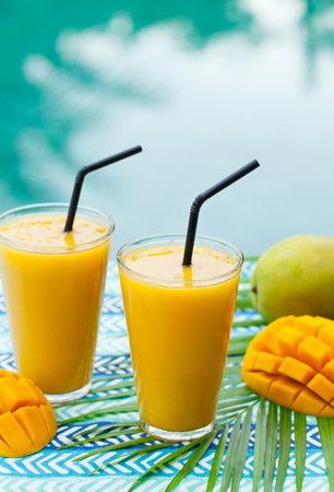 Fruit smoothie mango juice and fresh mango on a outdoor tropical