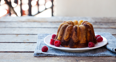 Chocolate marble bundt cake with raspberry on wooden Reklamní fotografie