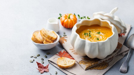 Pumpkin and carrot cream soup in bowl on grey stone