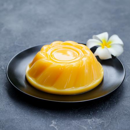 Mangopudding, Gelee, Dessert auf schwarzem Teller. Grauer Stein