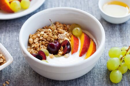 Healthy breakfast. Fresh granola, muesli with yogurt, fruits and berries on grey background. Close up.