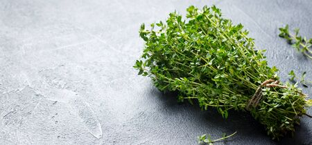 Fresh thyme bunch on slate background. Close up. Copy space. Imagens