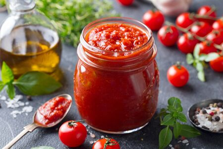 Tomato sauce in a glass jar with fresh herbs, tomatoes and olive oil.