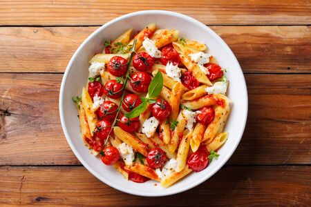 Pasta penne with roasted tomato, sauce, mozzarella cheese. Wooden background. Top view. Imagens