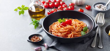 Pasta, spaghetti with tomato sauce in black bowl on grey background. Copy space. 版權商用圖片 - 134708255