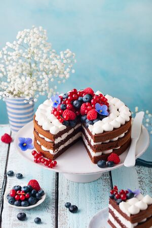 Chocolate cake with whipped cream and fresh berries. Blue wooden background. Copy space.