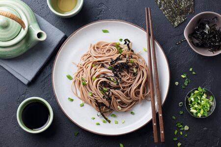 Soba noodles with sauce and garnishes. Japanese food. Top view. Black slate background.