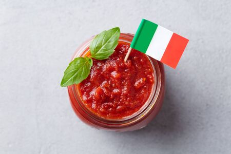 Tomato sauce with basil in a glass jar with Italian flag. Grey background. Top view. Close up.