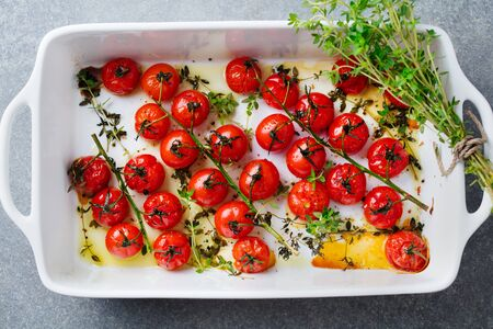 Roasted cherry tomatoes with herbs in baking dish. Grey background. Top view.