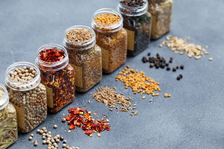Assortments of spices, white pepper, chili flakes, lemongrass, coriander and cumin seeds in jars. Copy space. Zdjęcie Seryjne
