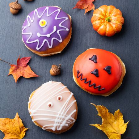 Donuts with Halloween decoration, icing on black slate background. Top view Stock Photo