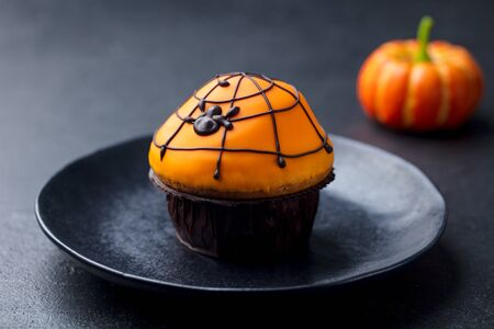 Halloween cupcakes with colourful decoration. Black slate background. Close up