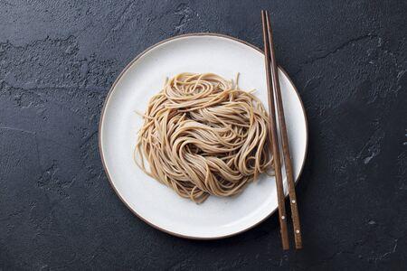 Soba noodles on a white plate. Japanese food. Black slate background. Top view. Banco de Imagens
